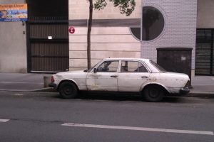 side view of beaten up Mercedes W123 in Paris