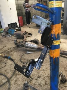gearbox crossmember hanging from transmission jack, in garage.